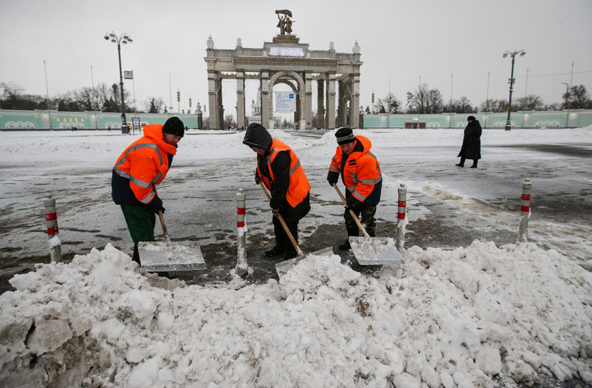 MOSCOW, RUSSIA. JANUARY 14, 2016. Workers shoveling snow in front of the main entrance to the VDNKh Exhibition Center. Artyom Geodakyan/TASS